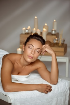 Young woman relaxing in spa salon.