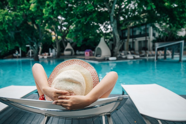 Young woman relaxing in swimming pool at spa resort.