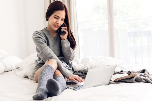 寝室で寒い冬の日にラップトップコンピューターを使用してリラックスした若い女性。ソーシャルアプリをチェックして働く女性。コミュニケーションとテクノロジーのコンセプト