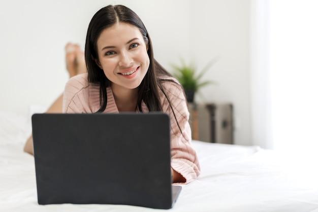 若い女性の寝室で寒い冬の日にラップトップコンピューターを使用してリラックス。ソーシャルアプリをチェックして作業。
