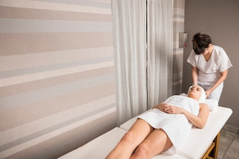 Young woman relaxing while beautician wrapping towel on woman's head at spa