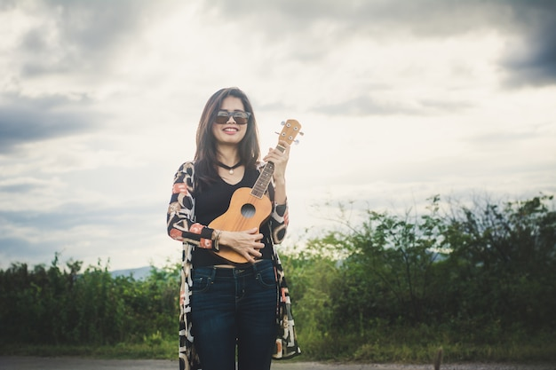 Young woman relaxing whit brown ukulele in the park.