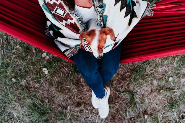 Молодая женщина отдыхает со своей собакой в гамаке