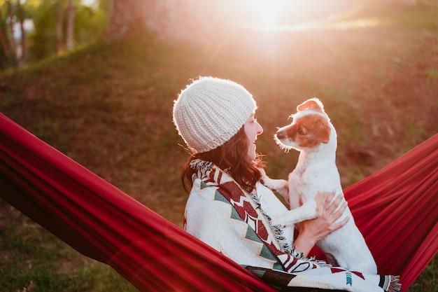 해먹에서 그녀의 강아지와 함께 편안한 젊은 여자