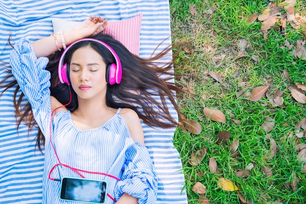 Young woman relaxing with listening music outdoor in garden.