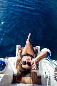 Young woman relaxing on the yacht on sea at sunny day