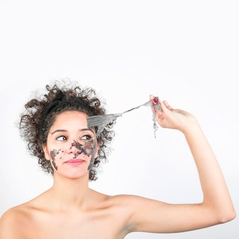 Young woman removing black mask on her face against white background
