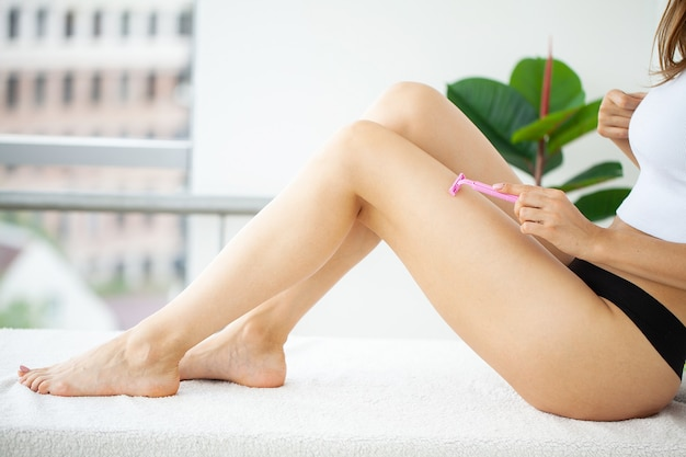Young woman removing hair on legs with razor at bathroom