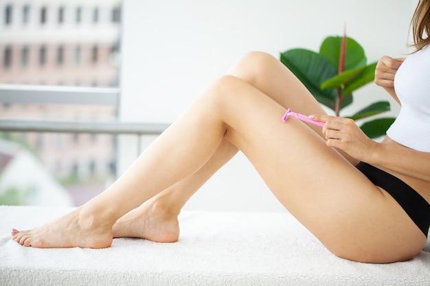화장실에서 면도기로 다리에 머리카락을 제거하는 젊은 여자