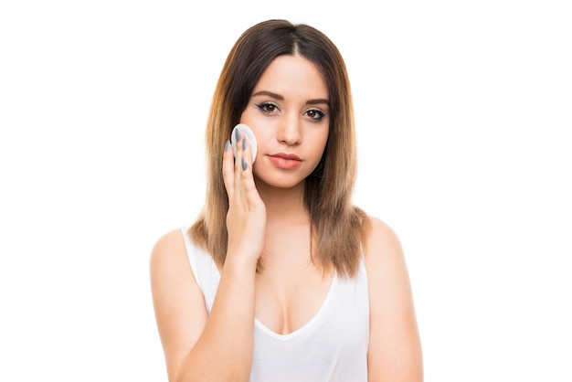Young woman removing makeup from her face with cotton pad