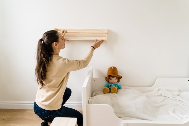 Young woman renovation child room in new house. wooden bookshelf. neutral nursery
