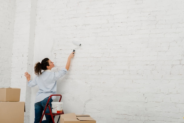 Young woman repainting wall