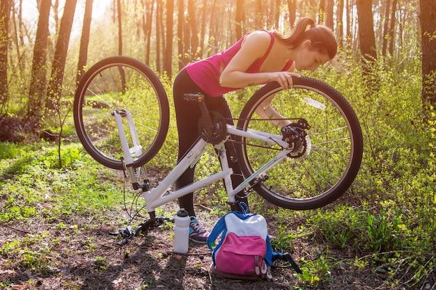 Молодая женщина ремонтирует велосипед в лесу