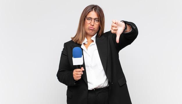 젊은 여성 기자가 십자가, 분노, 짜증, 실망 또는 불쾌감을 느끼고 심각한 표정으로 엄지 손가락을 보여주는