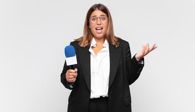 Молодая женщина-репортер чувствует себя счастливой, удивленной и веселой, улыбается с позитивным настроем, реализует решение или идею