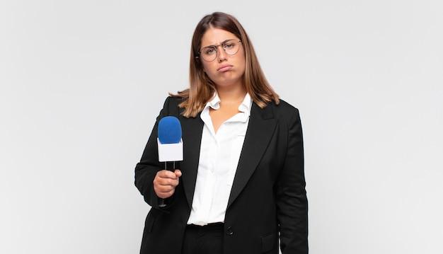 불행한 표정으로 슬프고 우는 소리를 느끼는 젊은 여성 기자는 부정적이고 좌절 된 태도로 울고 있습니다.