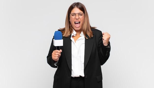 Молодая женщина-репортер агрессивно кричит с гневным выражением лица или со сжатыми кулаками, празднуя успех