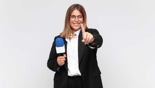 자랑스럽게 웃고 자신있게 넘버원 포즈를 만드는 젊은 여성 기자, 리더가 된 기분