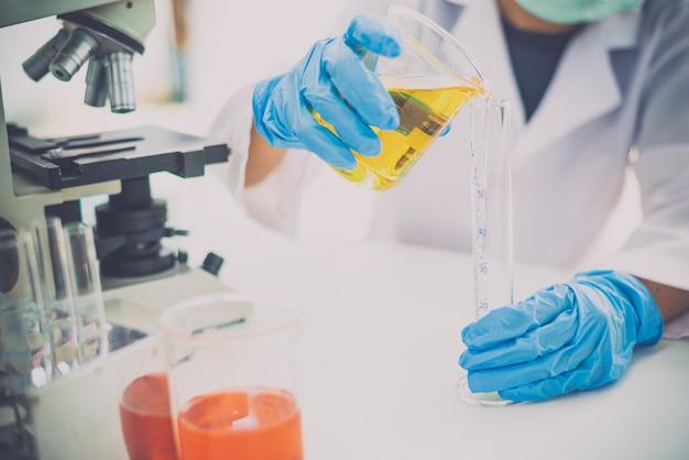 実験装置と科学実験を行う若い女性研究者は実験室で研究を行う黄色の試験管で油を注ぐ科学者を実験します。