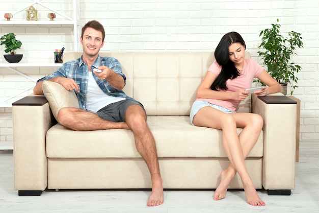 Young woman resentfully turned away from the guy who watches tv