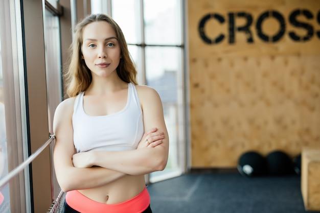 Giovane donna che riposa dopo l'allenamento in palestra. femmina fitness prendendo una pausa dopo la sessione di allenamento nel centro benessere.