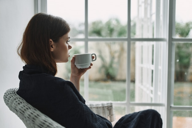Young woman resting on armchair at home by the window