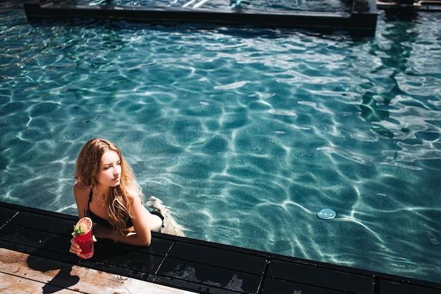 スイミングプールで休んで若い女性