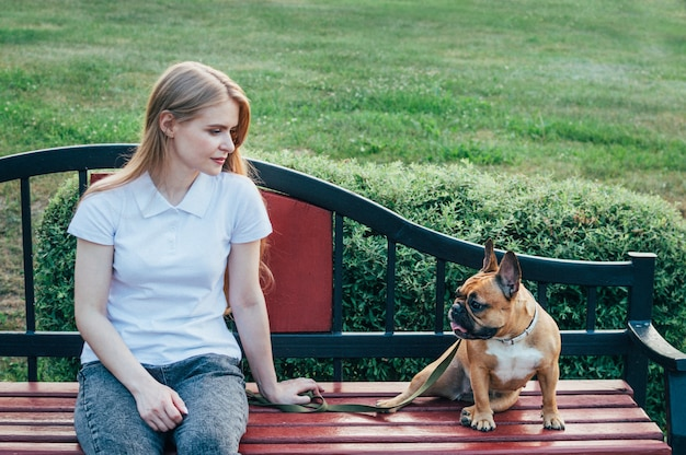 Young woman resting on a bench in the park with her dog in summer
