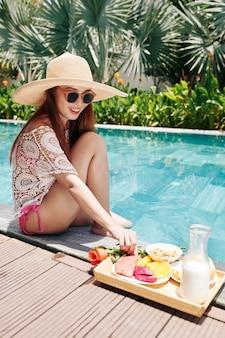 Молодая женщина, отдыхая у бассейна