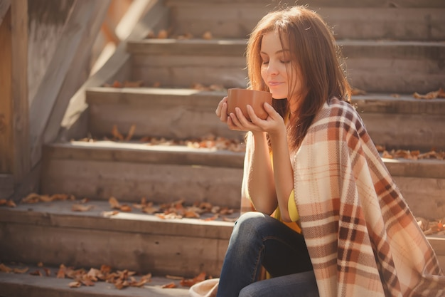 Young woman resting and drinking tea sitting in autumn garden on the steps, wrapped in a woolen plaid blanket