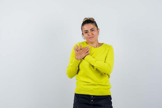 Giovane donna che riposa le mani sul petto in maglione giallo e pantaloni neri e sembra seria