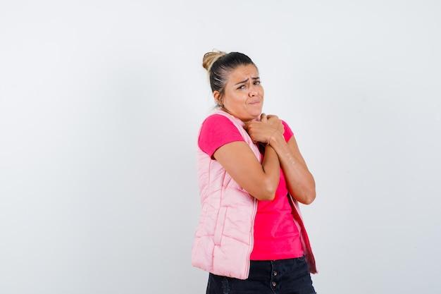 Молодая женщина, положив руки на грудь, дрожит в розовой футболке и куртке и выглядит измученной