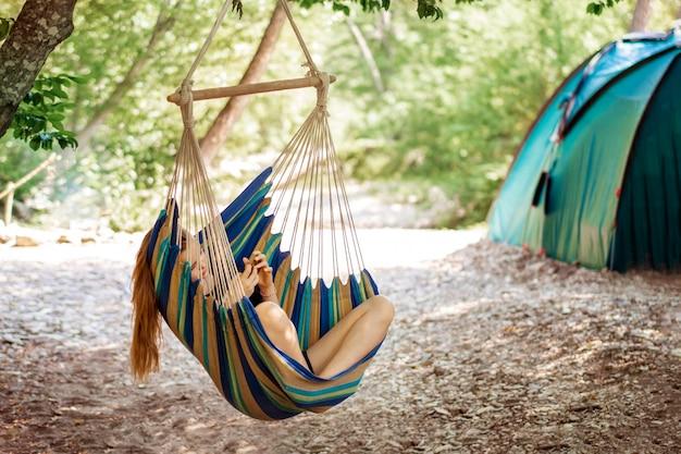 캠핑의 숲에 있는 해먹에서 쉬고 있는 젊은 여성
