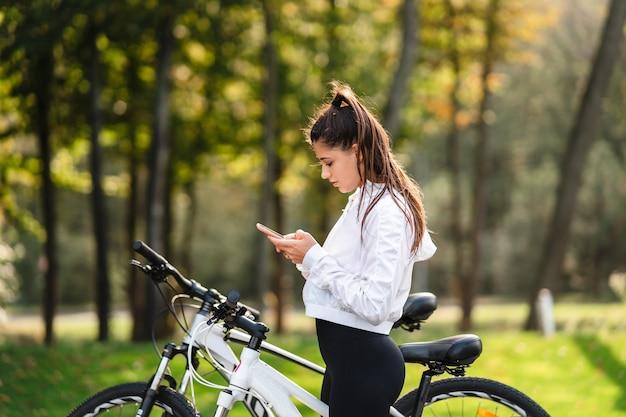 공원에서 휴식하는 젊은 여자는 화창한 날씨에 휴대 전화를 사용