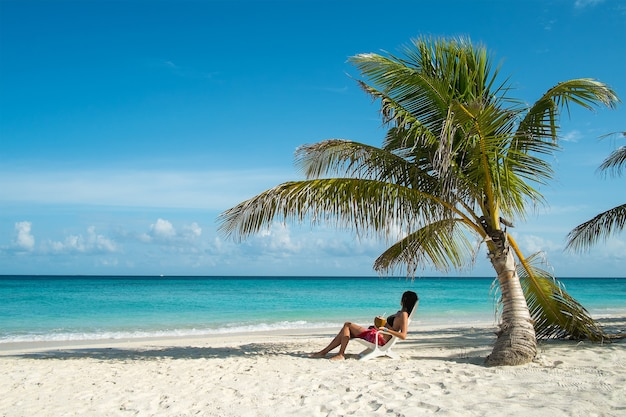 Young woman resting in a lounger under a palm tree by the ocean