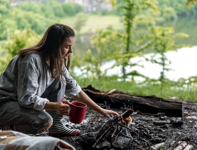 川の近くの森で暖かい飲み物のカップと火のそばで休んでいる若い女性