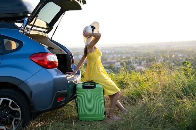여름 자연 속에서 그녀의 차 근처에 있는 녹색 가방에서 쉬고 있는 젊은 여성. 여행 및 휴가 개념입니다.