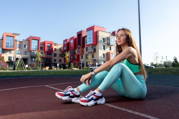여름날 공원에 있는 놀이터에서 쉬고 있는 젊은 여성. 펌핑된 근육을 가진 여자의 초상화입니다. 피트니스, 보디 빌딩, 에어로빅 개념입니다.