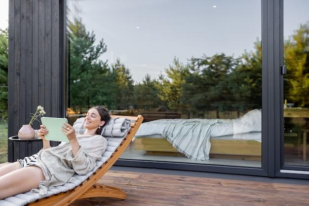 Молодая женщина отдыхает на шезлонге и читает на планшете на террасе в современном доме с панорамными окнами возле соснового леса. понятие уединения и отдыха на природе. велнес и внимательный курорт