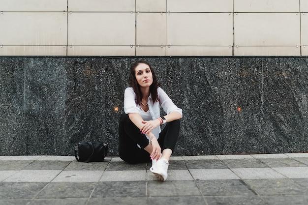 アスファルトで休んでいる若い女性。高品質の写真