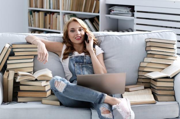 Молодая женщина отдыхает на диване, разговаривает по телефону