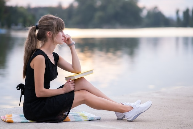 Young woman resting in summer park reading a book. education and sudy concept.