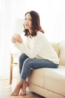 お茶を一杯で休む若い女性