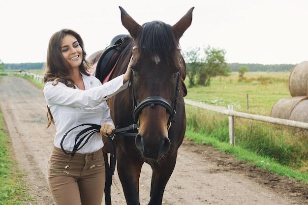 Всадник молодой женщины и ее красивая лошадь
