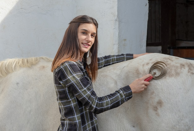 Young woman rider brushing the white horse