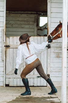 Young woman rider wearing a white shirt and hat leads her horse out of the stall for a walk.