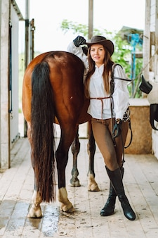 Young woman rider wearing a white shirt and hat with her brown horse in a stall portrait