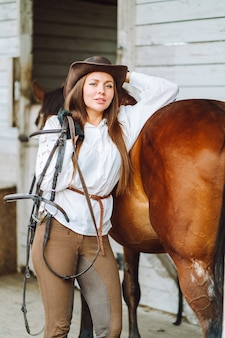 Young woman rider wearing a white shirt and hat with her brown horse in a stall, portrait.