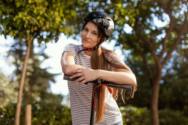 La giovane donna cavalca in uno scooter elettrico in un parco
