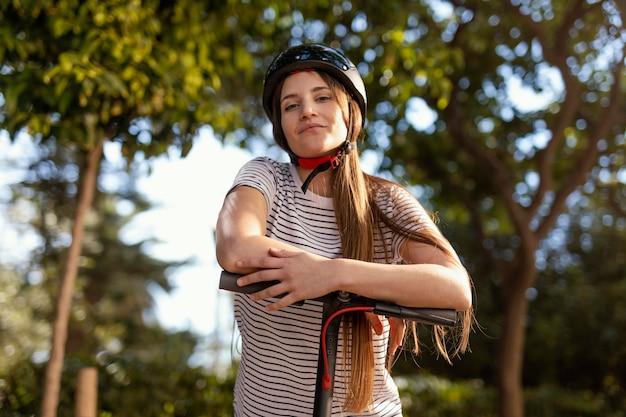 Молодая женщина едет на электросамокате в парке